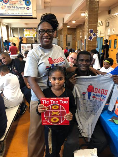 Assistant Principal, Ms. Roney, is handing out raffle prizes to our Dads Bring Your Child to School Day participants.